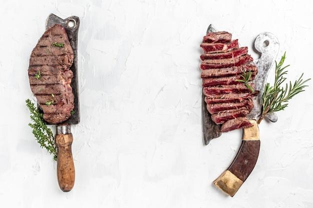 Свежий сырой стейк из говяжьей крупы prime black angus или стейк из говяжьей вырезки на старом мясном мясе на светлом фоне, баннер, место рецепта меню для текста, вид сверху.