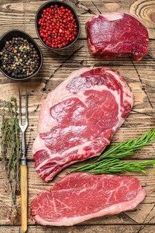 Fresh raw prime black angus beef steaks fillet mignon, rib eye or cowboy, striploin.
