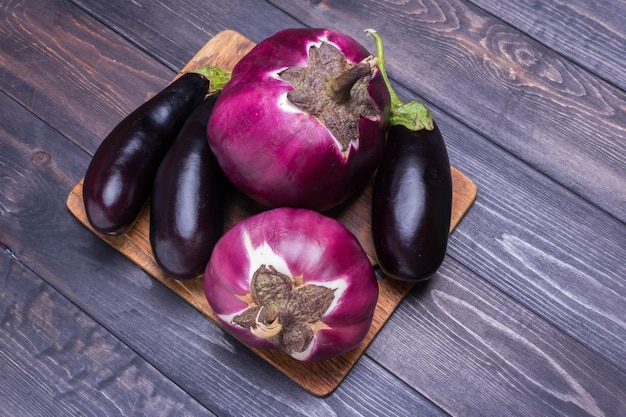 Fresh raw purple eggplant on a blue plate on gray wooden background flat lay