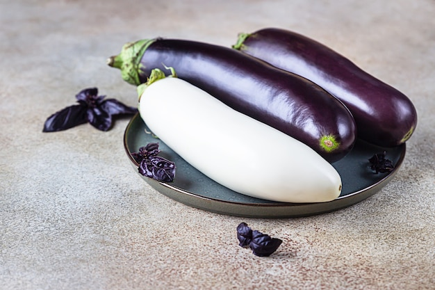 Fresh raw purple and white eggplant on a ceramic plate with purple basil