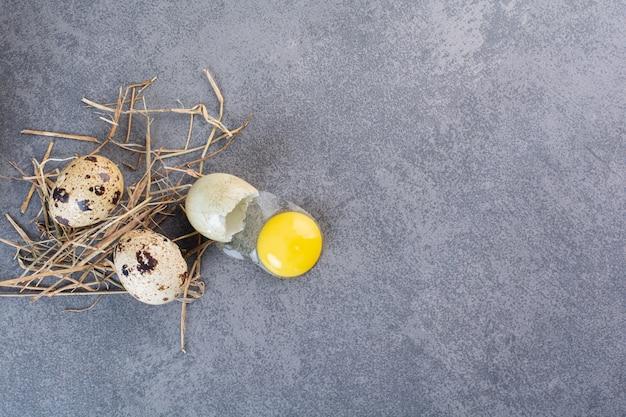 Fresh raw quail eggs placed on a stone table .