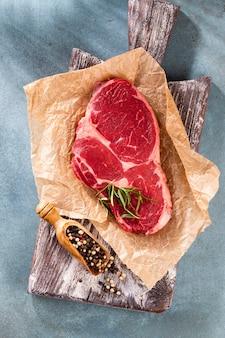 Свежий сырой стейк рибай на деревянной разделочной доске, со шпинатом, чечевицей и розмарином в деревенском стиле.