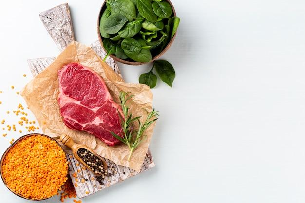 Fresh raw rib-eye steak on wooden cutting board