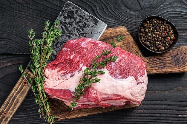 신선한 원시 라운드 로스트 비프 고기는 식칼로 정육점 커팅 보드에 잘립니다. 검은 나무 배경. 평면도.