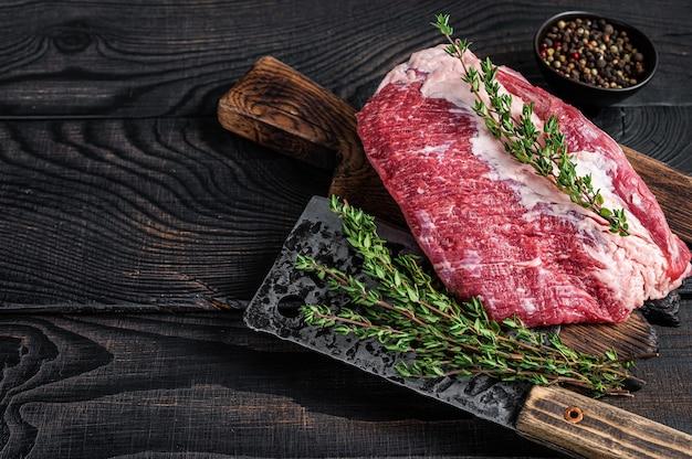 Свежее сырое круглое мясо ростбифа, нарезанное на разделочной доске мясника с помощью тесака. черный деревянный