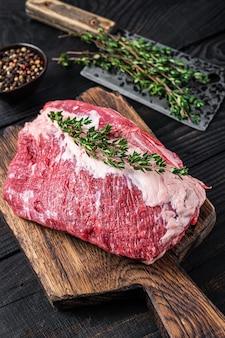 肉屋のまな板に包丁で切った新鮮な生の丸いローストビーフの肉