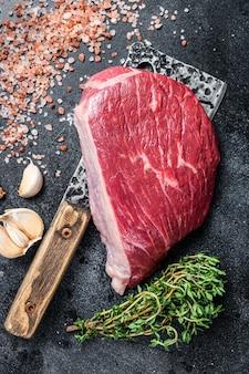 肉屋の包丁に新鮮な生のランプビーフカットまたはトップサーロインキャップステーキ。上面図。