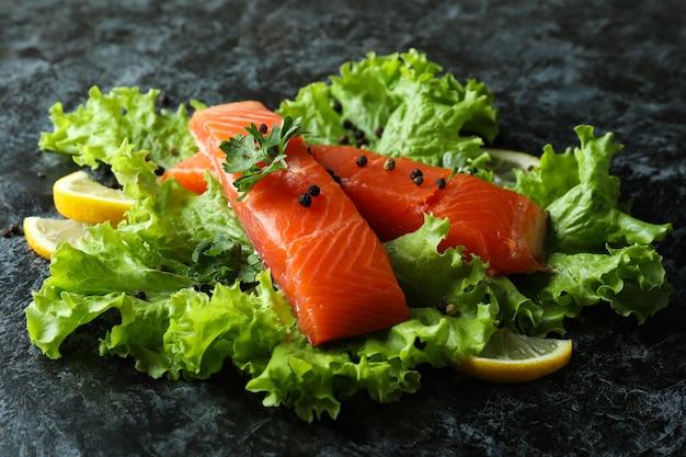Свежий сырой лосось и ингредиенты для приготовления на черном фоне дымчатого