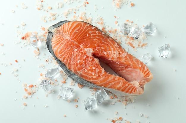 Свежий сырой лосось и специи на белом фоне