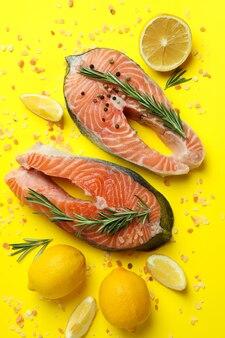 Свежий сырой лосось и специи на желтом фоне