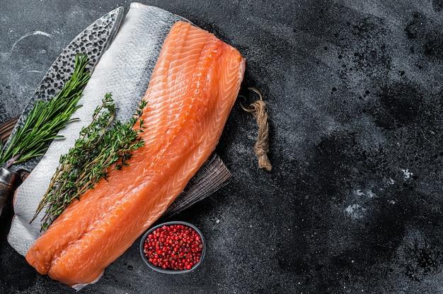 Свежая сырая рыба филе лосося на разделочной доске с ножом. черный фон.