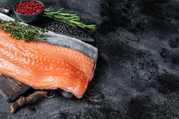 Свежее сырое филе лосося на разделочной доске с ножом