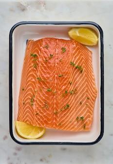 Свежее сырое филе лосося горбатого с ломтиками розмарина и лимона вертикально вверху