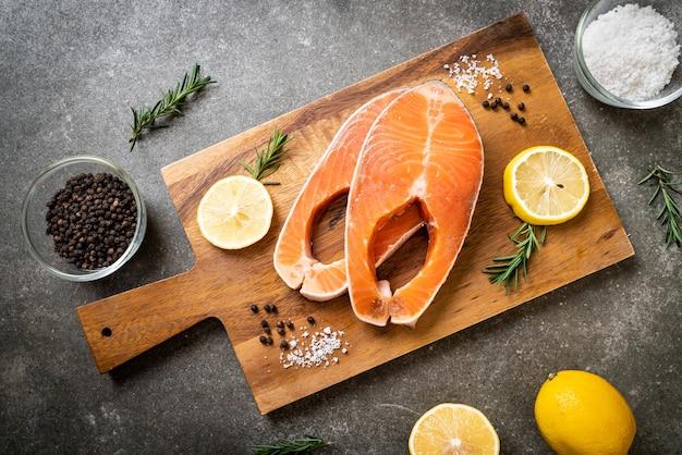 Стейк из свежего сырого филе лосося с ингредиентами на борту