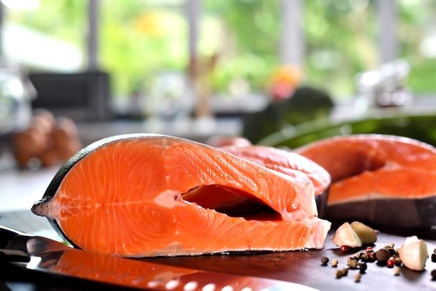 Стейки из свежего сырого филе лосося на разделочной доске на кухне
