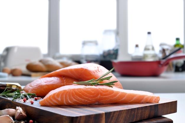 Стейки из свежего сырого филе лосося с ингредиентами на разделочной доске на кухне