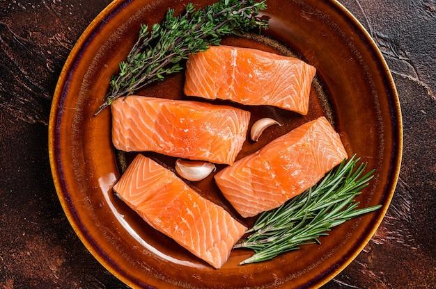 백리향과 로즈마리를 곁들인 소박한 접시에 신선한 생 연어 생선 필레 스테이크. 어두운 배경입니다. 평면도.