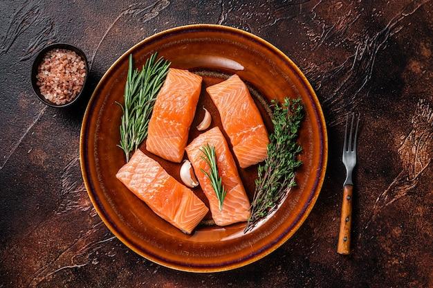 Свежие сырые стейки из филе лосося на деревенской тарелке с тимьяном и розмарином