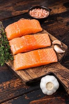 Свежие сырые стейки из филе лосося на деревянной доске с тимьяном