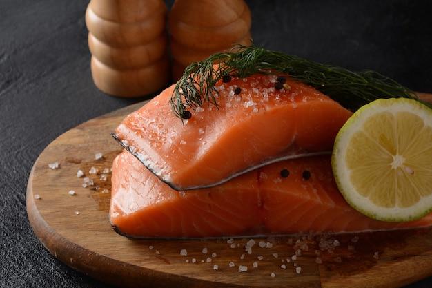 검은 배경에 요리 재료 허브와 레몬을 곁들인 신선한 생 연어 생선 필레