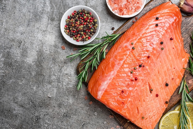 Fresh raw salmon fish fillet with cooking ingredients, herbs and lemon on gray concrete background. healthy diet food. top view