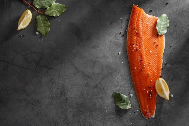 Филе свежей сырой рыбы лосося со специями на темном каменном фоне. креативный макет из рыбы, вид сверху, плоский