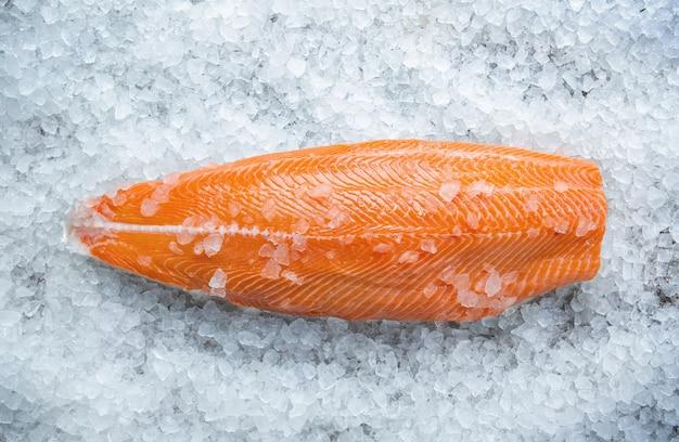 Свежий сырой стейк из лосося на льду на сером каменном фоне