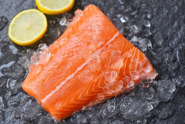Стейк из свежей сырой рыбы из лосося на льду с лимоном и темным камнем