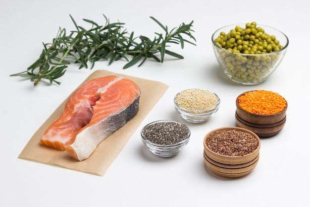 Fresh raw salmon, green peas, asparagus,  lemon, bulgur and chickpeas on table