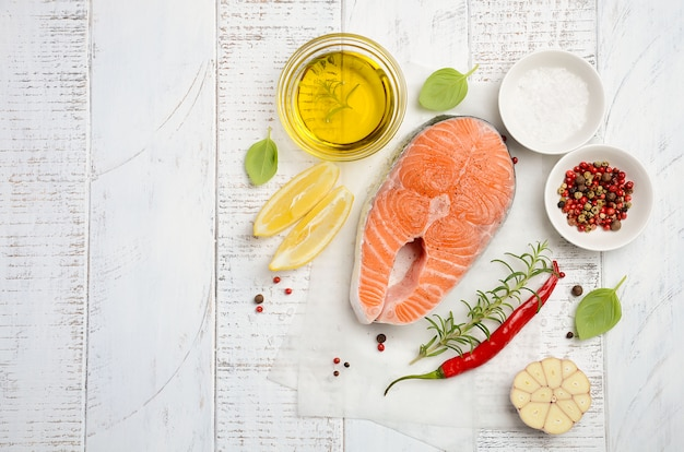 Fresh raw salmon steak with lemon, olive oil and spices on rustic wooden background.