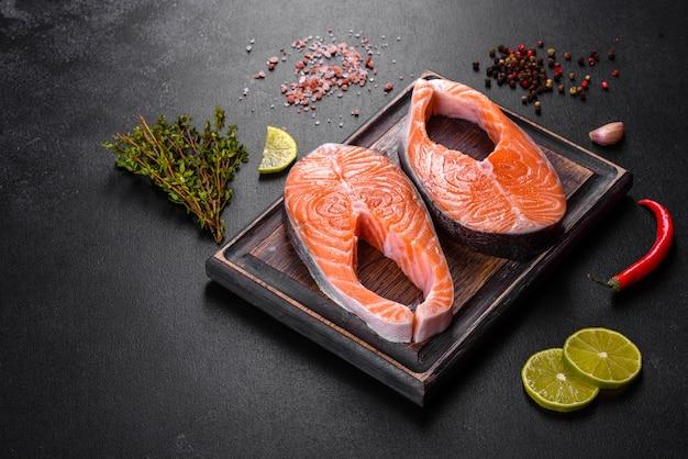Стейк из свежего сырого лосося со специями и зеленью, приготовленный для запекания на гриле. здоровая еда из морепродуктов