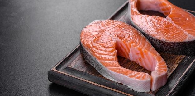 Стейк из свежего сырого лосося со специями и зеленью, приготовленный для запекания на гриле