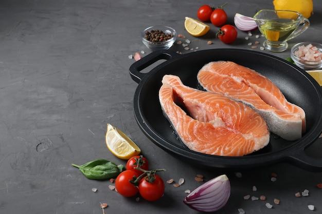 Свежие сырые стейки из лосося на сковороде для гриля и ингредиенты на темной поверхности