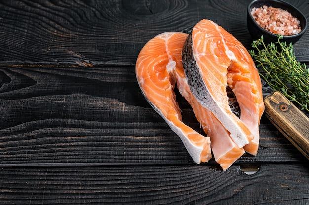 Свежие сырые стейки лосося на тесаке мясника. черный деревянный фон. вид сверху. скопируйте пространство.