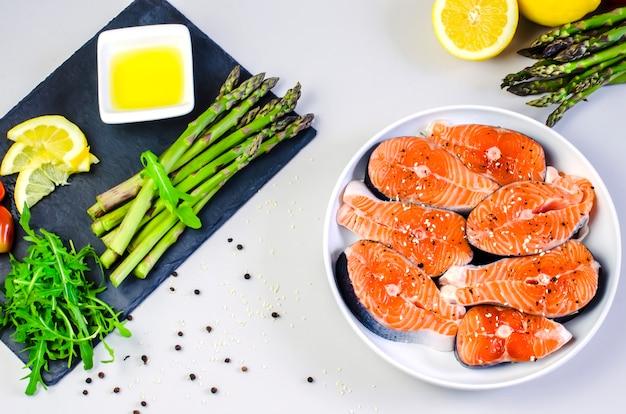 新鮮な生のサーモンステーキと野菜とスパイス:アスパラガス、トマト、胡pepper、ルコラ、レモン、グレーのテーブルにオリーブオイル。健康食品ダイエットコンセプト。