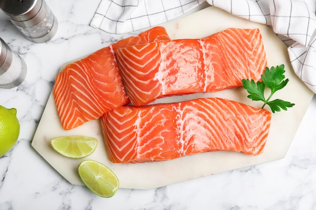 Fresh raw salmon with lime and parsley on white marble table, flat lay. fish delicacy