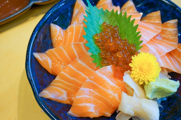 Fresh raw salmon with salmon eggs or ikura and wasabi on topped rice bowl (donburi) - japanese food style