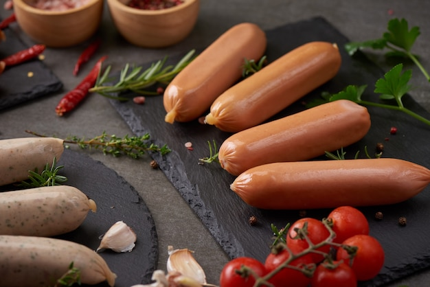 Свежие сырые колбасы и ингредиенты для приготовления. классические отварные сосиски из свинины на разделочной доске с перцем, розмарином, зеленью и специями.