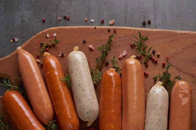 신선한 생 소시지와 요리 재료. 후추, 로즈마리, 허브 및 향신료와 함께 보드를 자르고 클래식 삶은 고기 돼지 고기 소시지.