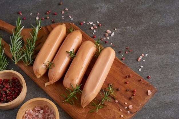 Свежие сырые колбасы и ингредиенты для приготовления. сосиски классические отварные из мяса свинины на разделочной доске с перцем,