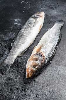 Свежая сырая рыба морского окуня. черный фон. вид сверху.