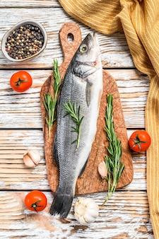 Fresh raw sea bass fish with herbs.
