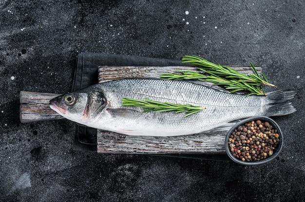 신선한 원시 바다 농 어 또는 농 어 요리에 대 한 준비가 나무 보드에. 검정색 배경. 평면도.
