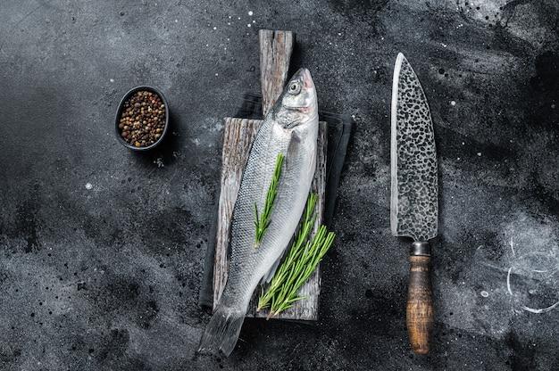 요리할 준비가 된 나무 판자에 있는 신선한 생 농어 또는 농어. 검은 배경. 평면도.