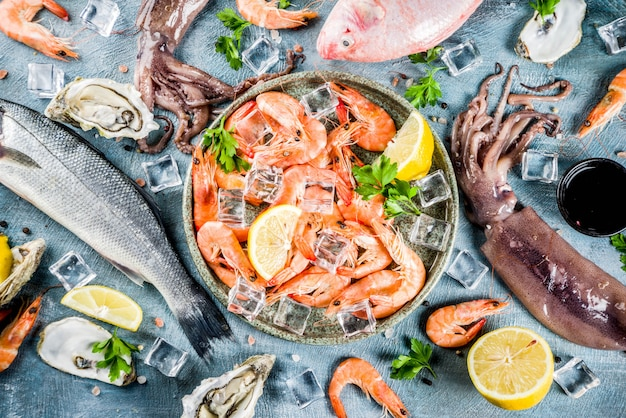 Fresh raw seafood squid shrimp oyster mussels fish with spices of herbs lemon on a light blue background