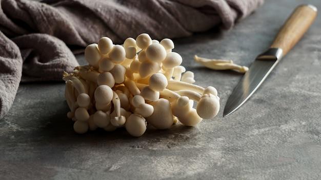 Fresh raw shimeji mushrooms on thr old wooden cutting board