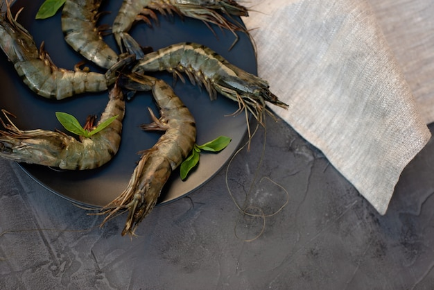 黒皿に新鮮なエビのエビ。健康的なシーフードはタンパク質の源です。フラット横たわっていた。コピースペース。