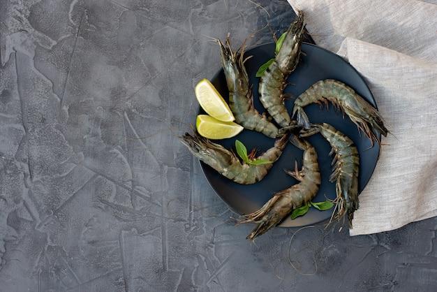 新鮮な生海老エビとレモンのブラックプレート。健康的なシーフードはタンパク質の源です。フラット横たわっていた。コピースペース。