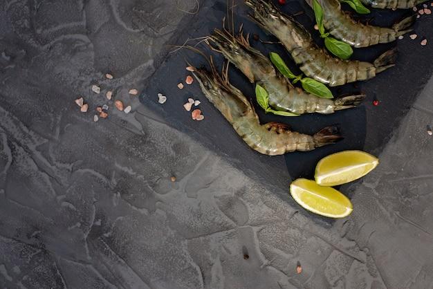 石灰ボードに石灰とスパイスが入った新鮮な海老エビ。健康的なシーフードはタンパク質の源です。フラット横たわっていた。コピースペース。