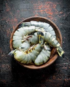 Свежие сырые креветки в деревянной тарелке. на темном деревенском